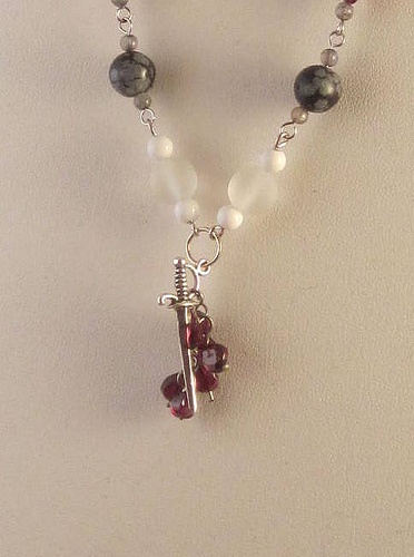 Close-up of pendant of necklace: several small dark red jewels pierced by a silvery sword