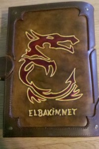 worked-leather logo of Elbakin, a stylized dragon in red
