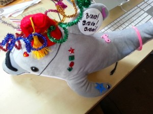 stuffed dolphin decorated with sparkly things and a button that reads BRAVO! BRAVO! BRAVO!